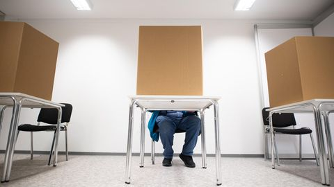 Hamburg: Ein Mann gibt in einer Wahlkabine seine Stimme ab.
