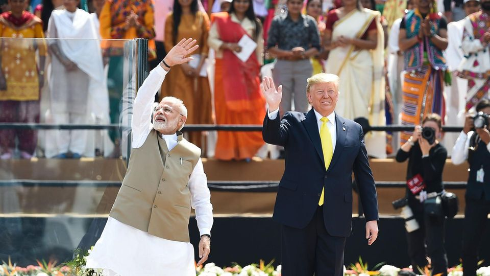 Auf einer Tribüne in einem Stadion stehen Narendra Modi und Donald Trump und winken Zuschauern zu