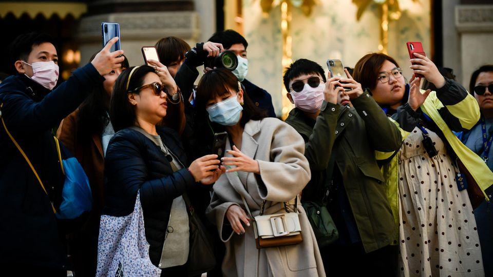 Touristen tragen Mundschutz und fotografieren mit ihren Smartphones
