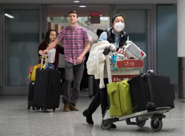 Am Flughafen:Eine Frau trägt eine Atemmaske neben ankommenden Reisenden ohne Mundschutz