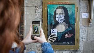 """Eine Frau fotografiert das Werk """"Mobile World Virus""""des Graffitikünstlers TV Boy in Barcelona."""