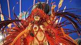 Trotz viel nackter Haut tragen manche Tänzerinnen mehrere Kilo schwere Kostüme auf dem Rücken durch das Sambódromo