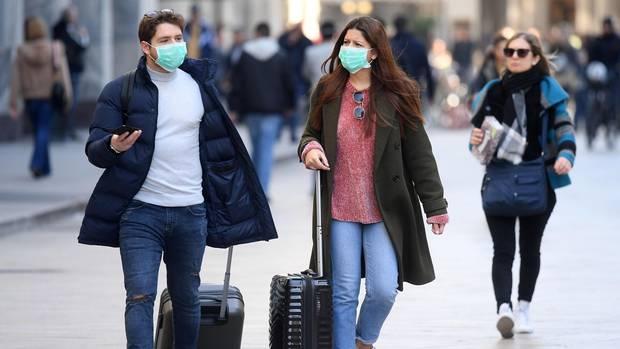 Touristen tragen Mundschutz und rollen ihre Gepäck. Angesichts der raschen Ausbreitung des neuen Coronavirus in Italien berät die italienische Regierung mit den Nachbarländern die Lage