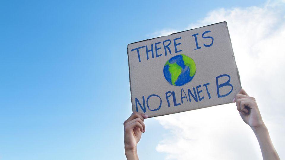 Klimafasten im Selbstversuch: Ein Mann hält ein Protestschild hoch