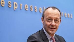 """Vor einer blauen Wand mit """"Bundespressekonferenz""""-Schriftzug sitzt Friedrich Merz in einem Anzug und lächelt."""