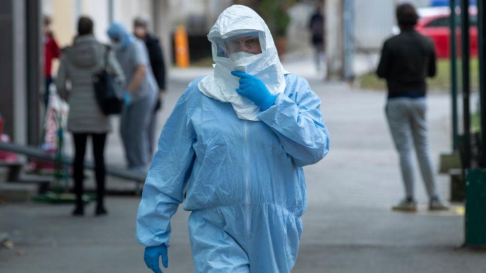 Ein Mitarbeiter der Klinik für Infektionskrankheiten trägt einen Schutzanzug