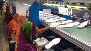 Frauen in bunten Gewändern legen weiße Schuhsohlen auf ein Fließband zwischen ihnen
