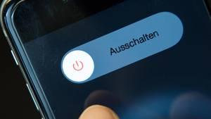 Fastenzeit: Daumen auf einem Smartphone-Display, das den Ausschalten-Button zeigt