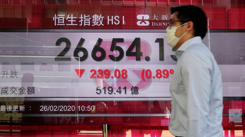 Ein Mann geht an einer Anzeigentafel der Hongkonger Börse vorbei.