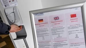Am Eingang zur privaten Hochschule Diploma in Hessen kann man neben einem Coronavirus-Warnschild seine Hände desinfizieren