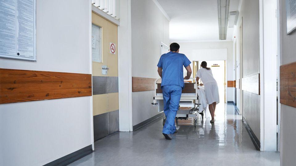 Ärzte schieben einen Verletzen in einem Bett durch einen Krankenhausflur
