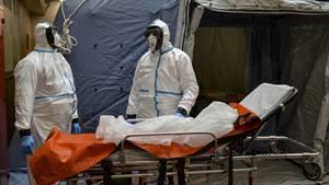 Turin: Zwei Mitarbeiter in Schutzanzügen stehen in einem Krankenhaus neben einer Liege
