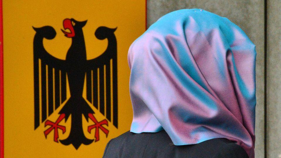 Eine junge Frau mit Kopftuch geht an einem Behördenschild mit dem Bundesadler vorbei