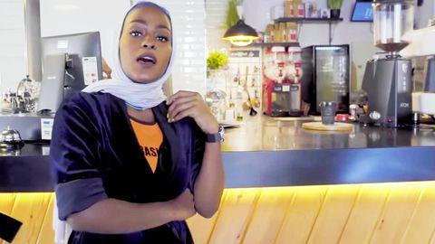 Vor dem Tresen eines Cafés steht eine junge Frau mit Kopftuch und rappt
