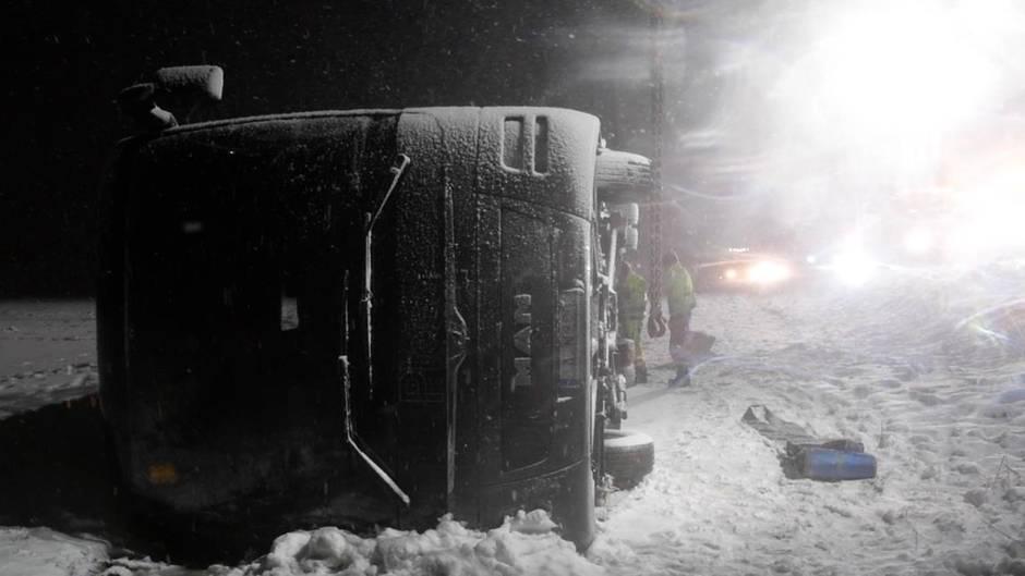 Auf einer verschneiten Autobahn liegt ein Reisebus im Dunkeln auf der rechten Seite