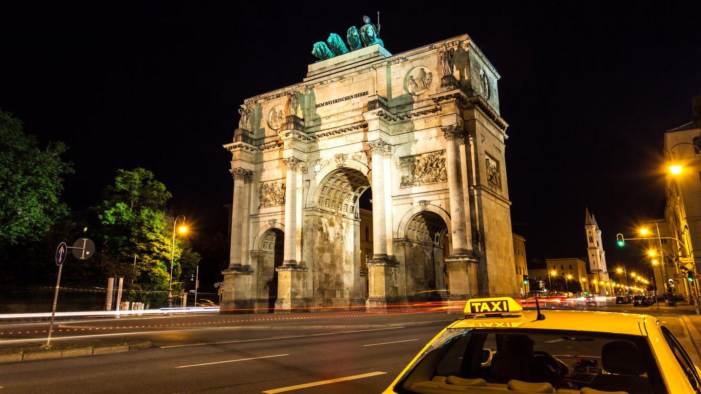 Ein Taxi steht nachts vor dem Siegestor in München