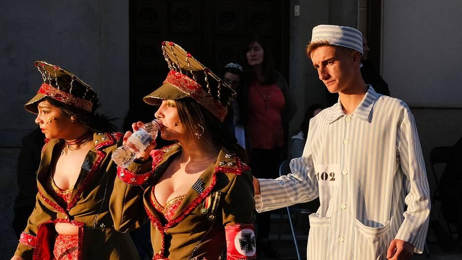 Zwei Frauen mit tiefen Ausschnitten gehen in SS-Uniformen vor einem Mann in KZ-Kleidung