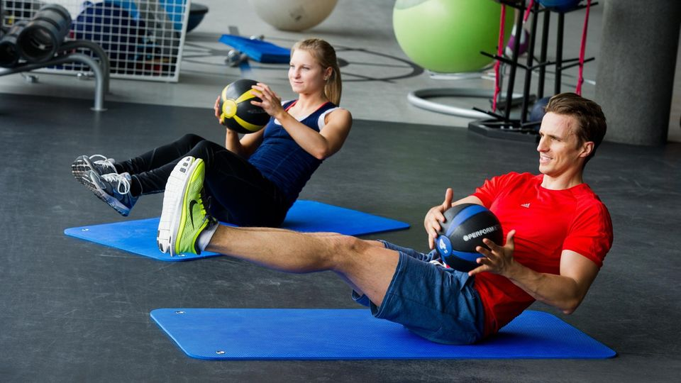 Functional training: A woman and a man doing functional training in a gym