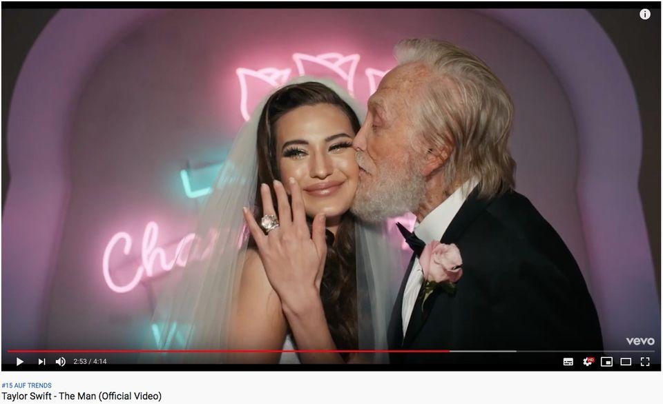 """Ausschnitt aus dem Musikvideo zu """"The Man"""": Eine Braut hält ihre beringte Hand in die Kamera"""