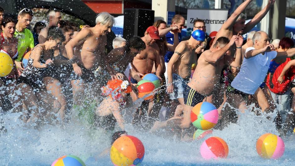 Männer und Frauen in Badekleidung springen zugleich in ein Freibad-Becken, in dem Wasserbälle treiben