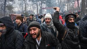 Migranten rufen und gestikulieren im türkisch-griechischen Grenzgebiet