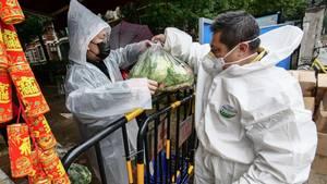 Ein Mann versorgt einen Bewohner Wuhans mit Gemüse