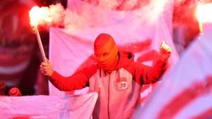 Ein Bayern-Fans mit brennenden Bengalos