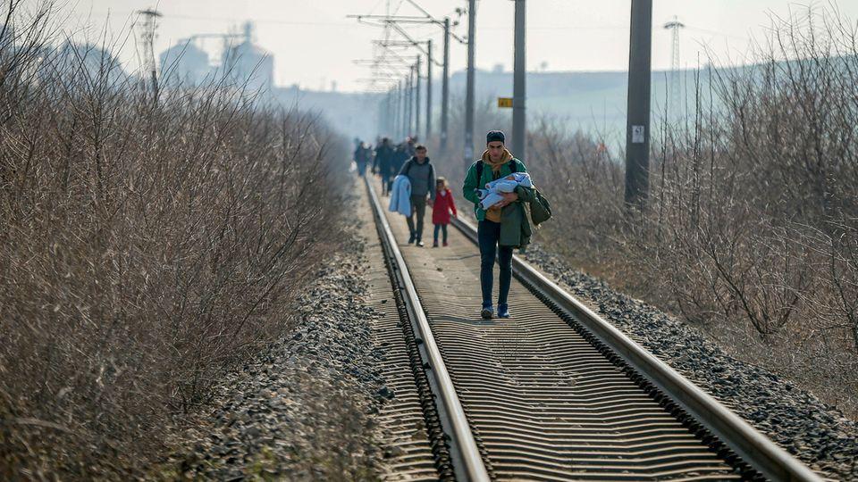 Migranten gehen an Schienen entlang Richtung der türkischen Grenze zu Griechenland