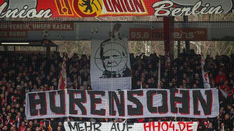 """Im Stadion An der Alten Försterei haltenUnion-Fans Banner mit dem Schriftzug """"Hurensohn"""" und dem Abbild von Dietmar Hopp hoch"""