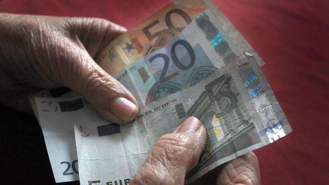 Die Hände einer alten Frau halten einen 50-, einen 20- und einen 5-Euro-Schein