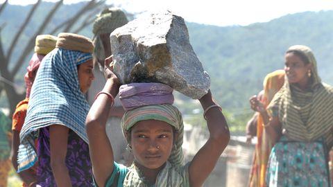 Ein Mädchen in bunten Gewand balanciert auf ihrem Kopf einen großen Steinbrocken