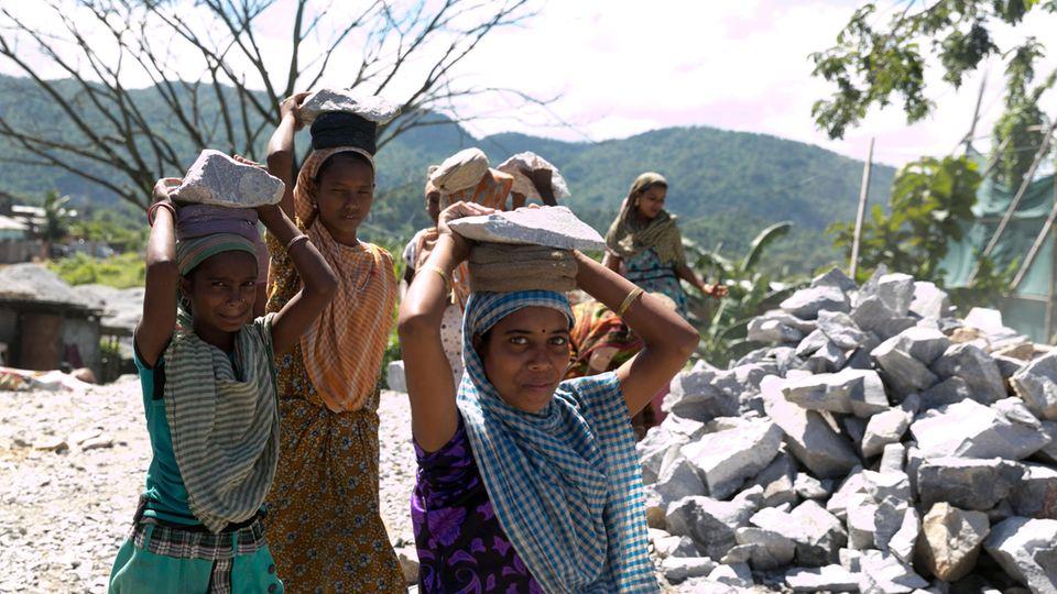 Kinder schleppen oft Steine zu einer Mühle, die Schotter und Kies herstellt