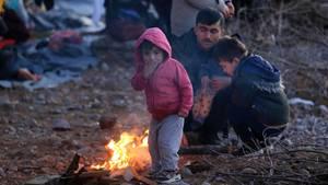 Migranten, die aus der Türkei eingetroffen sind, wärmen sich auf der Insel Lesbos an einem Feuer