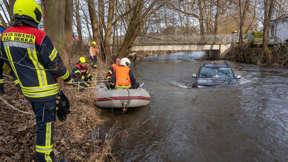 Die Feuerwehrleute versuchen ein Auto aus der Ilm zu bergen.