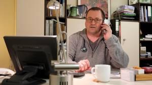 Hausarzt Coronavirus: Ein Arzt sitzt am Schreibtisch und telefoniert