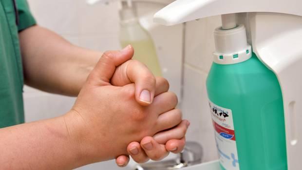 Eine Mann in Krankenhauskleidung reibt sich die Hände vor einem Desinfektionsmittel-Spender