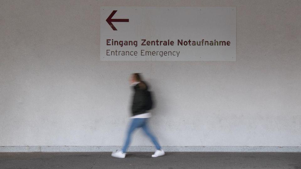 """Unter einem Wegweiser """"Eingang Zentrale Notaufnahme"""" geht eine junge Frau in Richtung des Pfeils"""