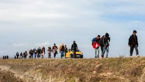 Migranten gehen in der Nähe des Grenzüberganges in Edirne eine Straße entlang