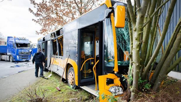 Ein beschädigter Bus steht nach einem Unfall in Troisdorf bei Köln vor einem Lastwagen