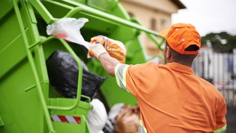 Müllmann wirft Müllsäcke ins Fahrzeug