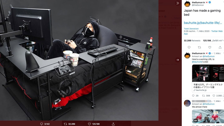 Ein junger Mann liegt in einem Bett, das mit Bildschirmen, Konsole und Tastatur ausgestattet ist