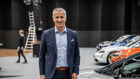 Ein großer Mann mit grau-weißem Seitenscheitel und blauem Anzug steht in einer Messehalle neben einer Reihe Autos