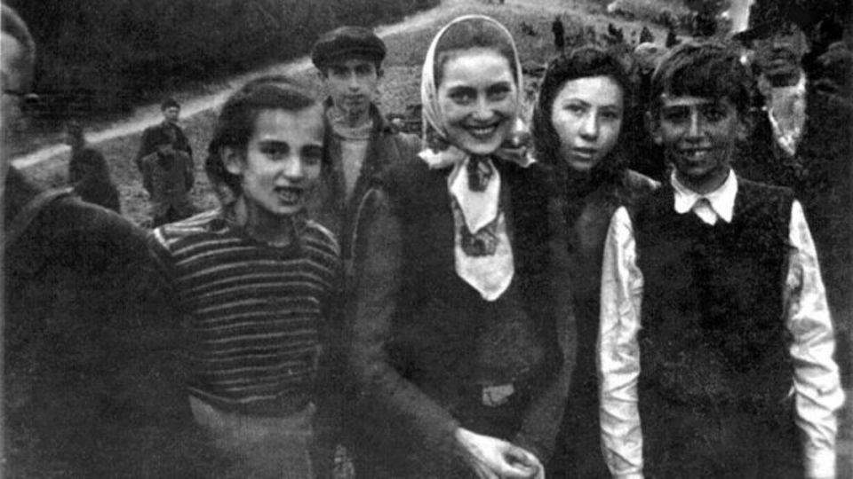 """Die ursprüngliche Notiz heißt: """"Das kleine Mädchen in der Mitte ist so schwach vom Verhungern, dass sie kaum noch stehen kann, um ein Lächeln für ihre 'Befreier' zu haben. Man könnte genau dasselbe von den beiden Kindern auf beiden Seiten sagen""""."""