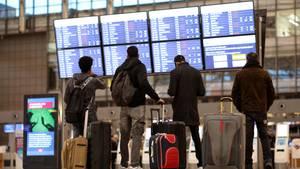 Ist mein Flug pünktlich? Passagierestehen vor einer Anzeigetafel im Terminal einesFlughafens.