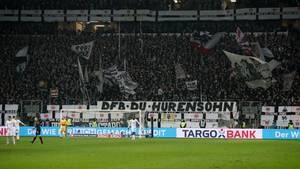 """Am Zaun in einem Fußballstadion hängt ein weißes Banner mit schwarzer Schrift: """"DFB Du Hurensohn"""""""