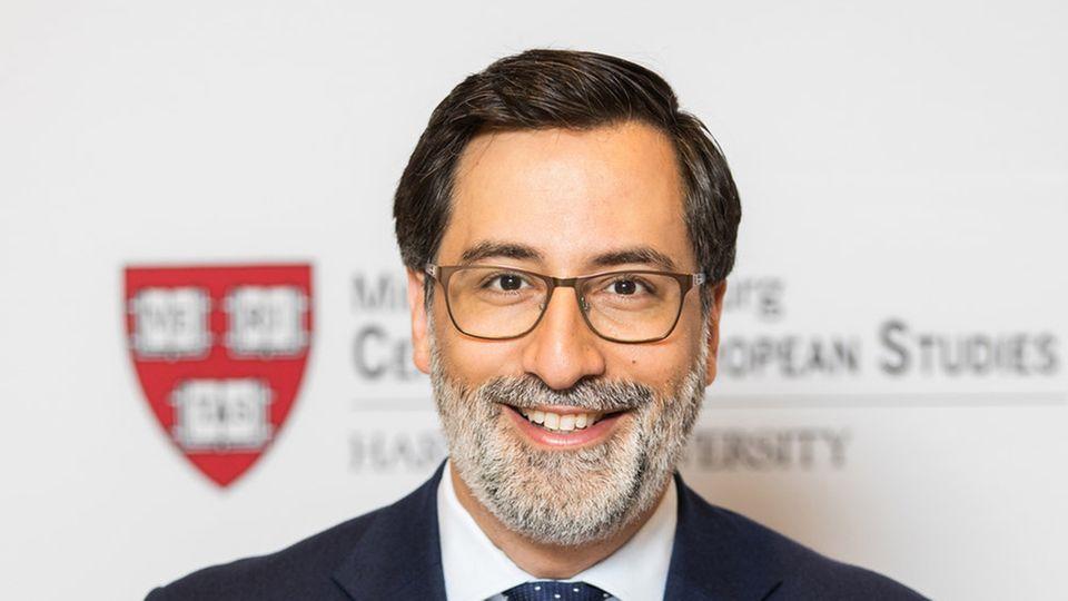 Ein Mann mit Brille, schwarzem Seitenscheitel und grauem Vollbart sitzt im Anzug vor einer Wand mit dem Logo der Uni Harvard