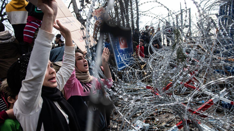 Frauen mit Kopftüchern stehen mit erhobenen Armen vor einer Stacheldrahtrolle und rufen