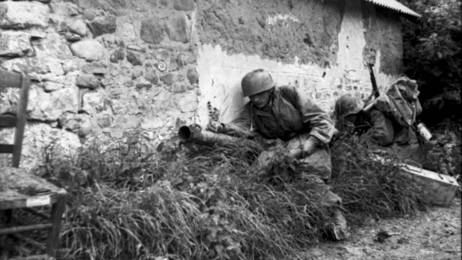 Deutsche Fallschirmspringer mit dem Panzerschreck in der Normandie. Der Schütze sucht die Deckung durch das Gebäude.