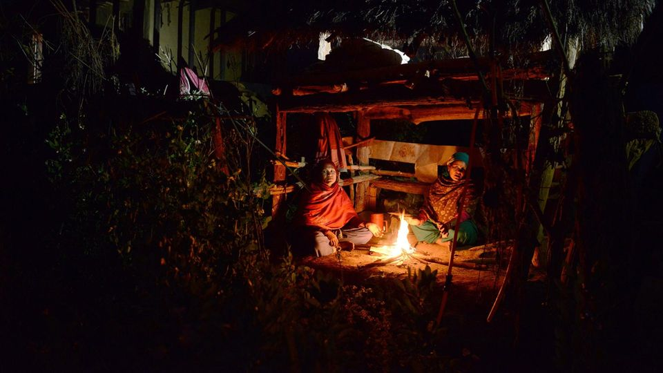 Zwei Frauen in bunten Gewändern sitzen nachts an einem Feuer vor einer einfachen Hütte