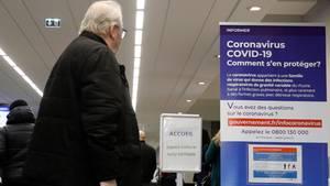 Ein älterer Herr liest in einem Krankenhaus in Creteil die Infotafel zum Coronavirus